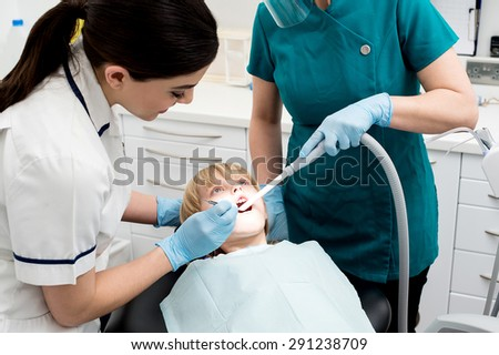 Dentist and assistant curing little girl