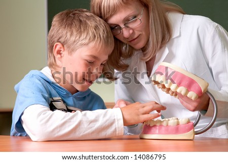 Dentist and boy with jaw of dentist's sample teeth - stock photo