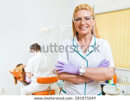 Dentist and her assistant examining teeth at dental office - stock photo