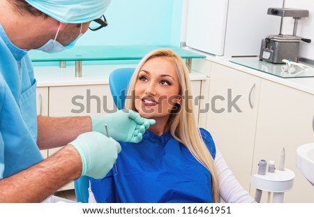Dentist and his patient talking in examination room - stock photo