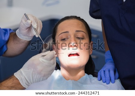 Dentist and nurse examining a scared patient in dental clinic - stock photo