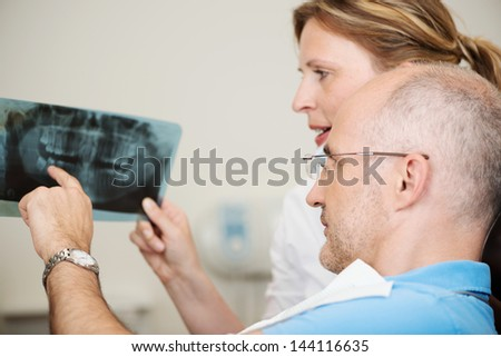 Dentist and patient are looking at x-rays - stock photo