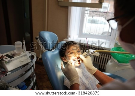 Dentist and Patient in Dentist Office. Child in the Dental Chair. Dental Treatment