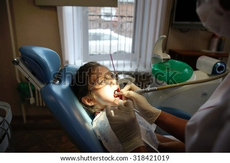 Dentist and Patient in Dentist Office. Child in the Dental Chair. Dental Treatment - stock photo
