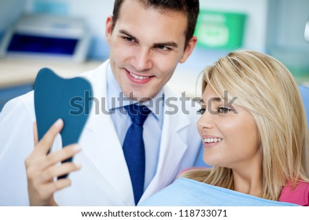 Dentist and satisfied patient with white teeth as a results of whitening treatment - stock photo