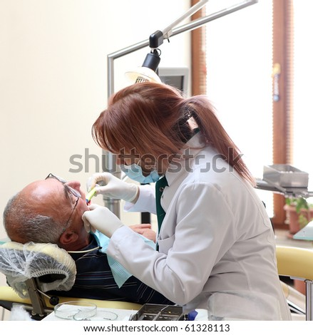 Dentist at work in dental room - stock photo