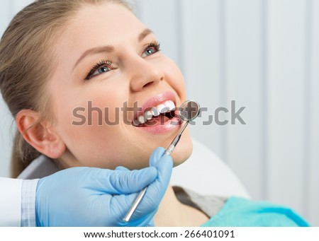 Dentist checking patient teeth looking in dental mirror. Oral procedure concept.  - stock photo