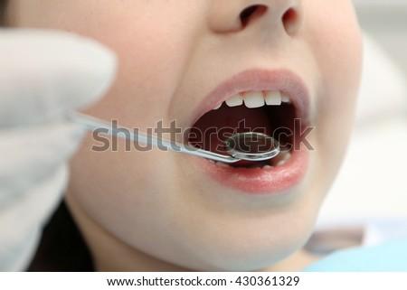Dentist checking up teeth health, close up - stock photo