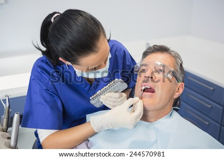 Dentist comparing teeth whitening of her patient in dental clinic - stock photo