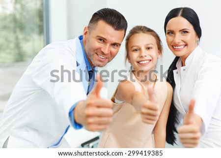 Dentist doctor,  assistant and little girl all smiling at camera with thumbs up at the dental clinic - stock photo