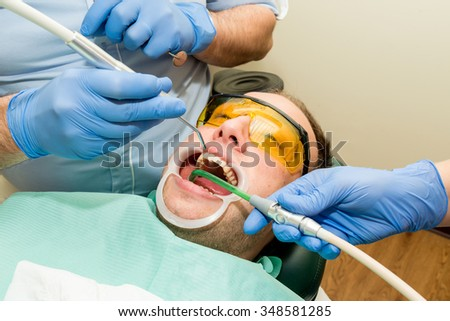Dentist doing a dental treatment on a patient - close up