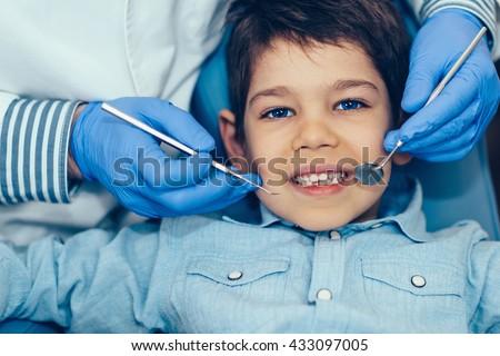 Dentist doing regular dental check-up to little boy. - stock photo