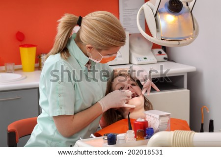 Dentist  examine  tooth of a young patient using tools, real people