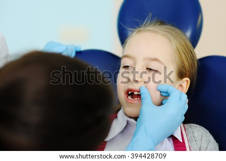 dentist examines teeth baby girl - stock photo
