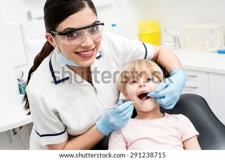 Dentist examining a little girl patient - stock photo