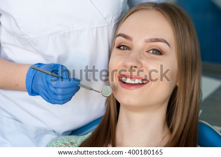 Dentist examining a patient's teeth - stock photo