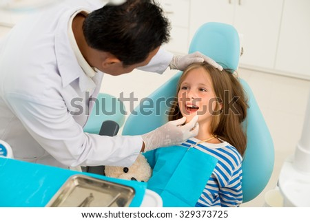 Dentist examining teeth and gums of little girl - stock photo