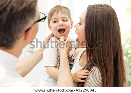 Dentist examining teeth of little boy holded by his mother at dental clinic - stock photo