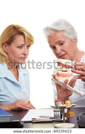 Dentist explaining treatment to woman on a teeth model - stock photo