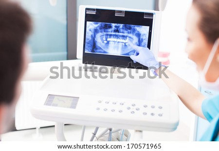 Dentist explaining x ray picture to patient  - stock photo