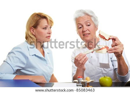 Dentist explains tooth care on a teeth model - stock photo