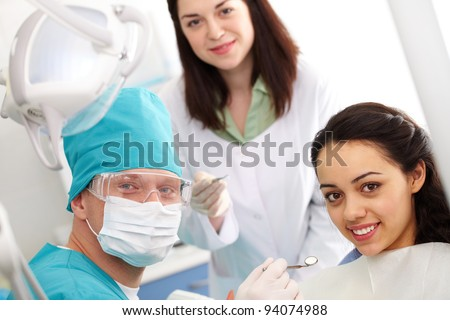 Dentist, his assistant and a patient looking at camera and smiling - stock photo