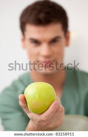 Dentist holding an apple out to the viewer, shallow depth of field, focus on apple - stock photo