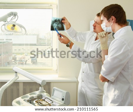 Dentist holding an x-ray and standing near chair - stock photo