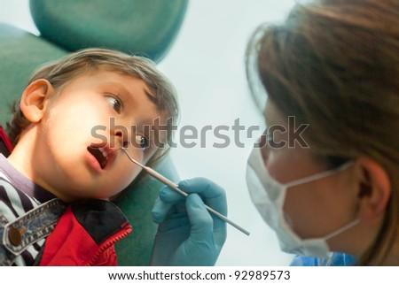 Dentist looking at a little boys teeth - stock photo