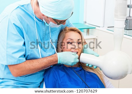 Dentist make jaw x-ray image for girl in dental clinic - stock photo