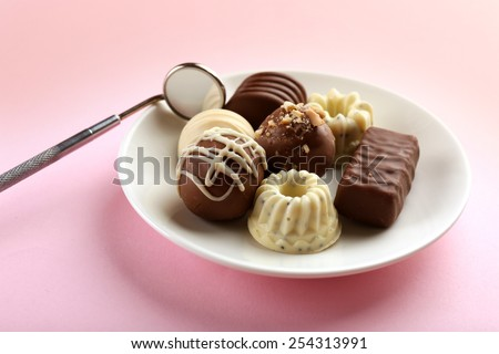 Dentist mirror with sweets on plate on pink background - stock photo