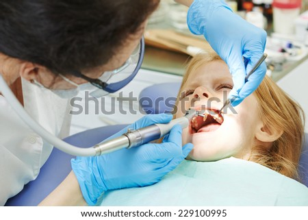 dentist orthodontist female doctor making dental care to child patient at working place - stock photo