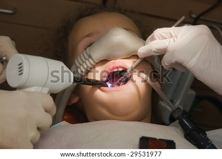 dentist performs a procedure of care for teeth child - stock photo