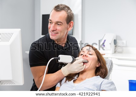 Dentist scanning patient's teeth with CEREC (Chairside Economical Restoration of Esthetic Ceramics) scanner - stock photo
