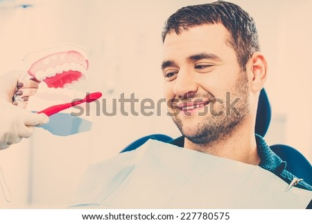 Dentist showing to man patient on mockup how to clean teeth - stock photo