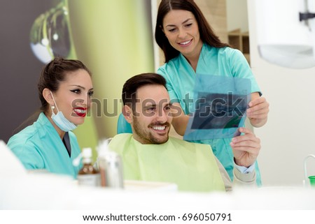 Dentist shows a patient x-ray image