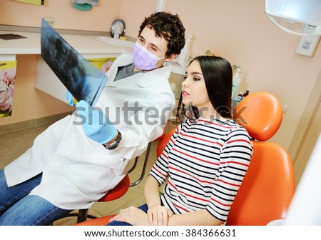 Dentist shows a patient x-ray picture of teeth