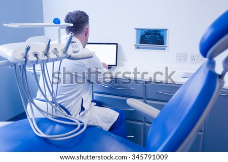 Dentist sitting and using computer in dental clinic