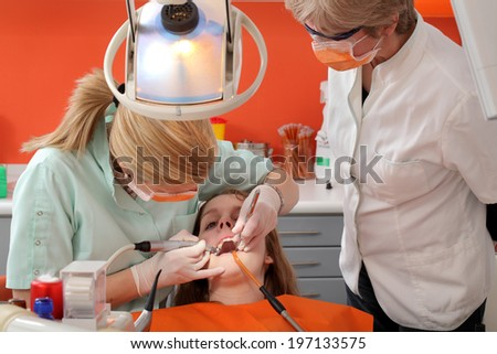 Dentist student drilling  tooth of a young patient with professor looking, real people - stock photo