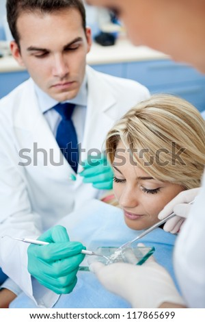 Dentist take dental powder from glass plate for preparing fillings - stock photo