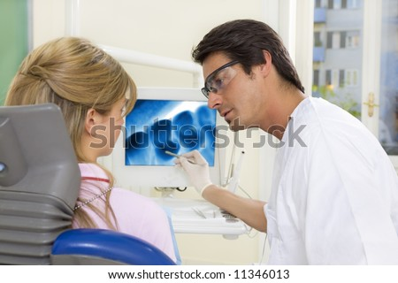 dentist talking to his patient and showing her a x-ray image of her teeth - stock photo