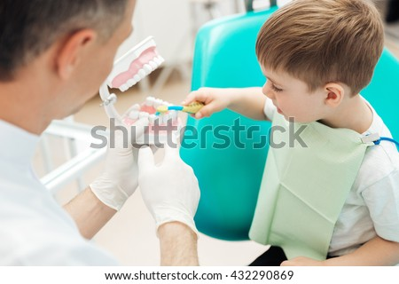 Dentist teaching cute little boy bruching teeth with toothbrush in dental clinic
