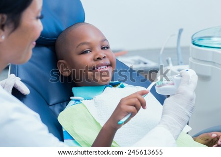 Dentist teaching happy boy how to brush teeth in the dentists chair - stock photo