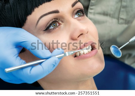 Dentist tools at work. Dentist makes the process of treatment of a beautiful young girl. - stock photo