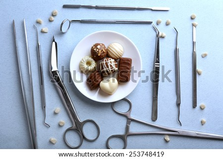 Dentist tools with sweets and teeth on light background - stock photo
