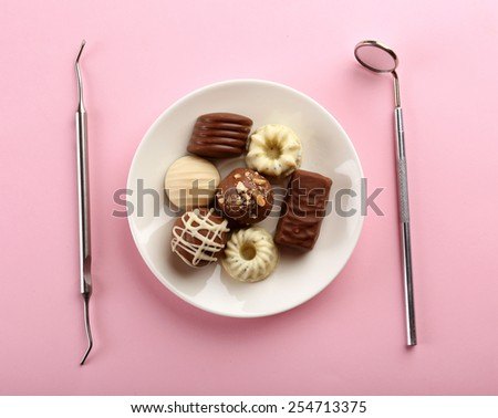 Dentist tools with sweets on plate on pink background - stock photo