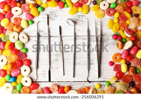 Dentist tools with sweets on wooden background - stock photo