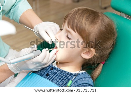 dentist treats teeth of a little girl. caries prevention