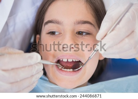 Dentist using dental explorer and angled mirror in mouth open of a patient - stock photo