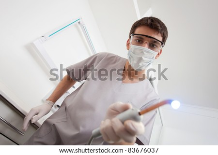 Dentist wearing mask holding medical equipment